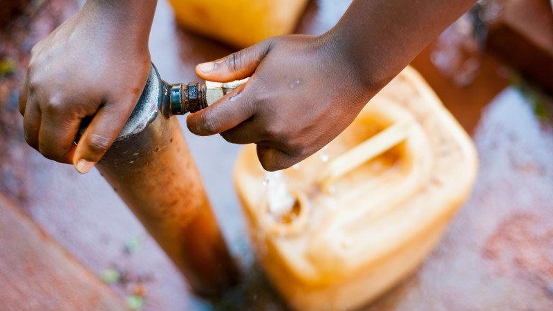 Hands on a water pump with a jerry can